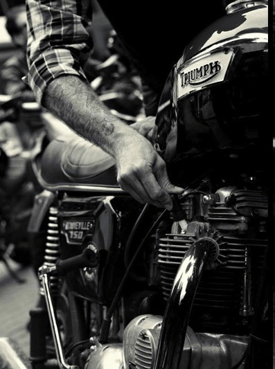 man checking spark plug on triumph motorcycle