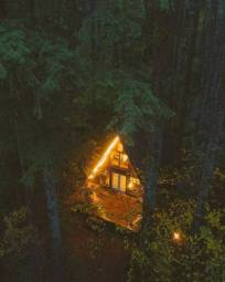 a frame cabin in the woods with lights