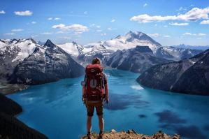 backpacker looking at lake and snow covered mountains