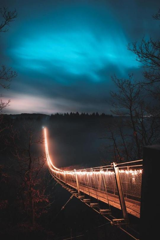 foggy foot bridge lit up from one end to another