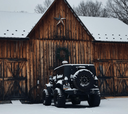 jeep parked outside wood barn with snow
