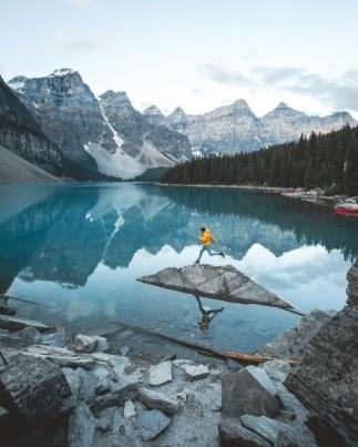 man jumping on rock on cold mountain lake