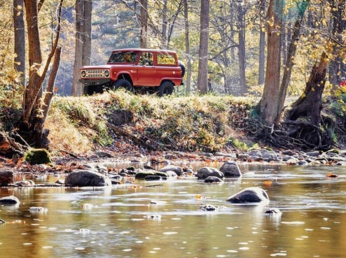 red ford bronco by a stream