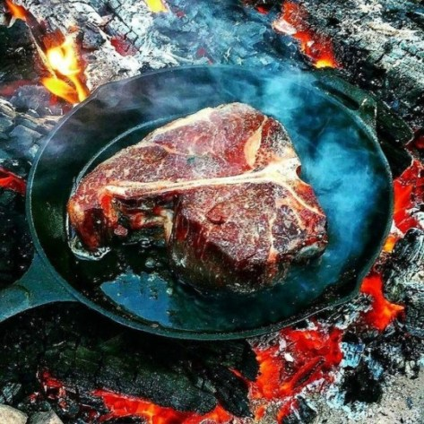 t bone steak being cooked on a cast iron pan outdoors