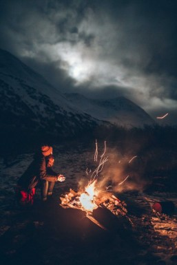 woman near campfire with dramtic night sky in background