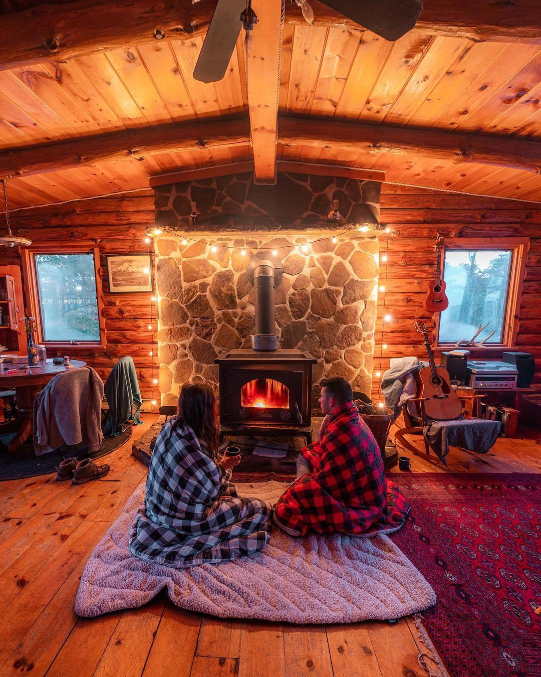 man and woman in front of wood burning stove cozy