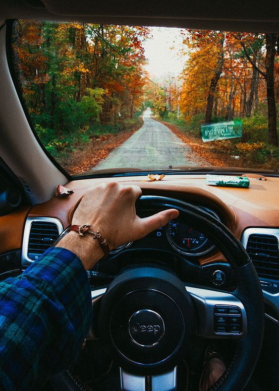 man driving jeep down country road in fall