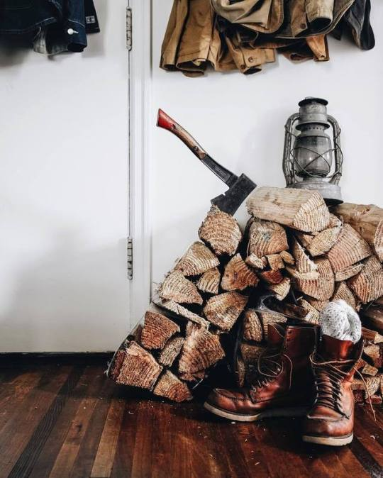 old boots next to firewood with axe