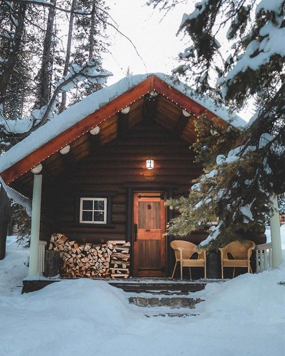 winter cabin with firewood on porch