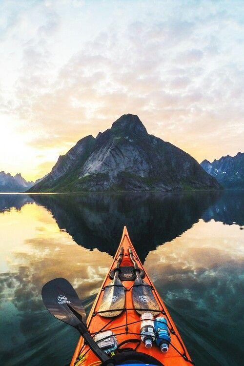 man paddling canoe in mountain lake