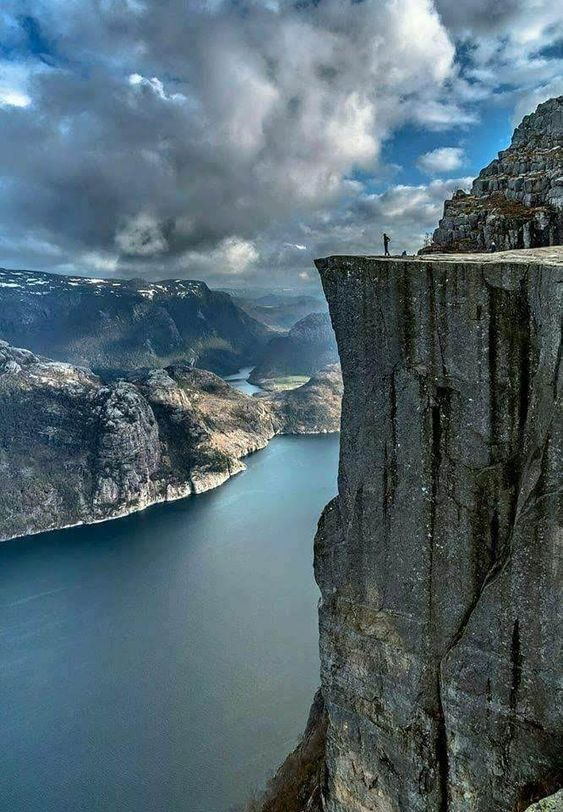 a man standing near the edge of a tall mountain cliff