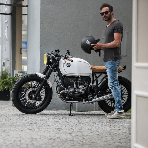 man standing next to cafe style bmw motorcycle