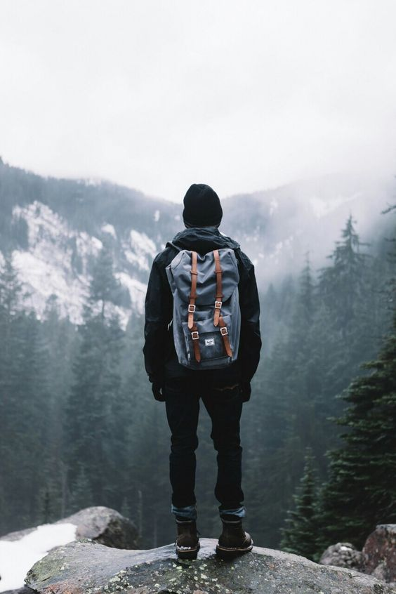 man standing on edge of mountain