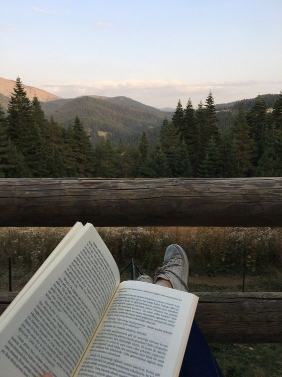 reading on deck with mountain scenery