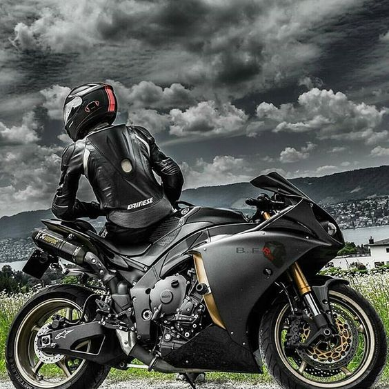man sitting on motorcycle with dramatic sky in background