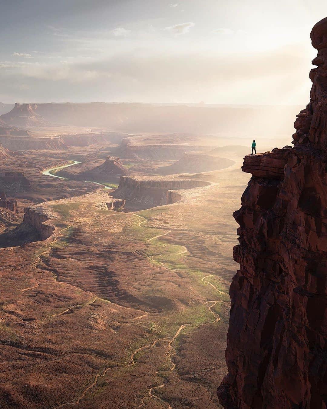 man standing on cliff in Utah