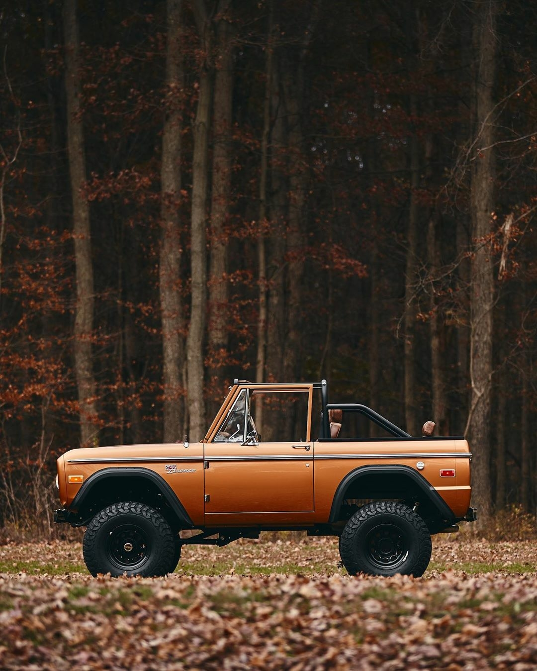 orange ford bronco in the woods