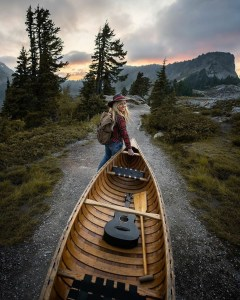 the manly life - woman helping carry a canoe in the pacific northwest