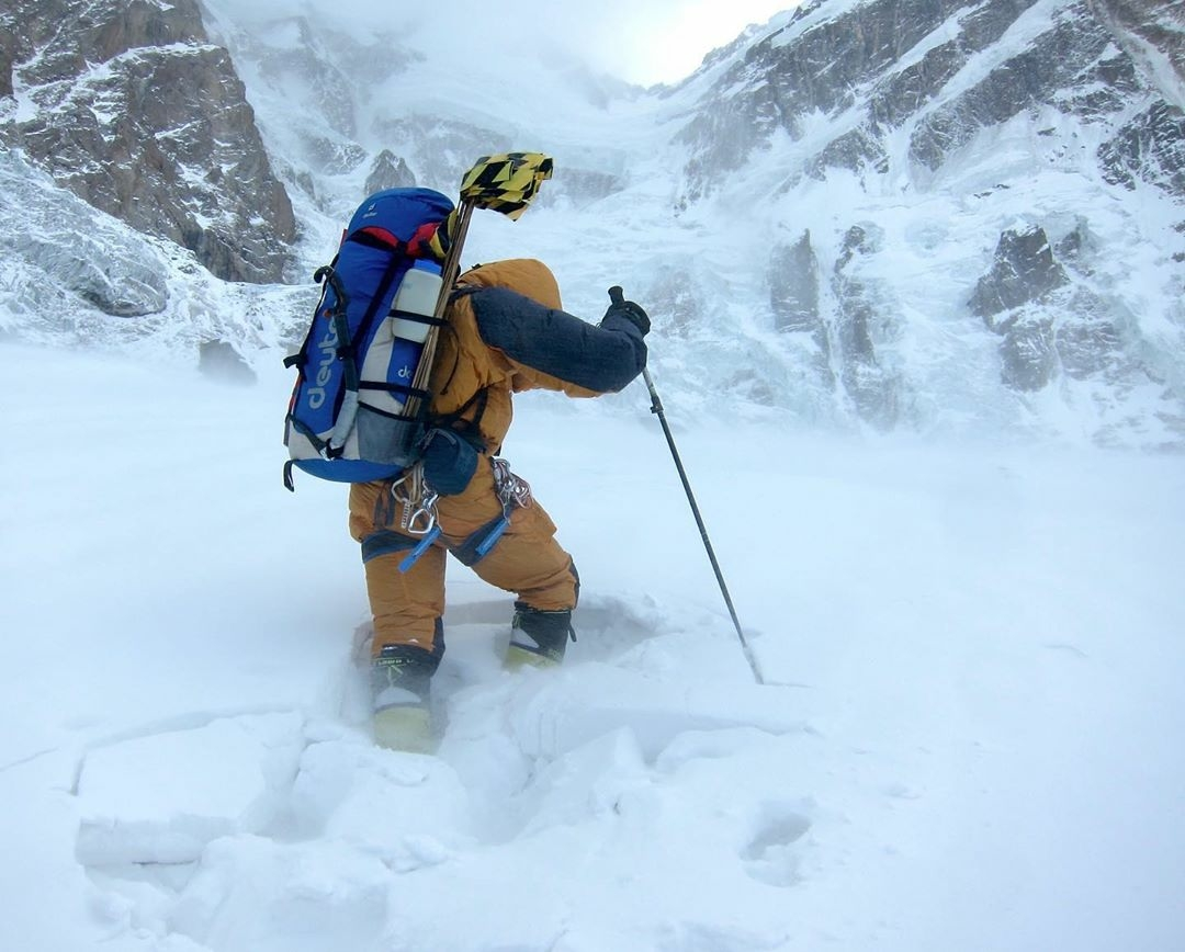 man mountain climbing through snow