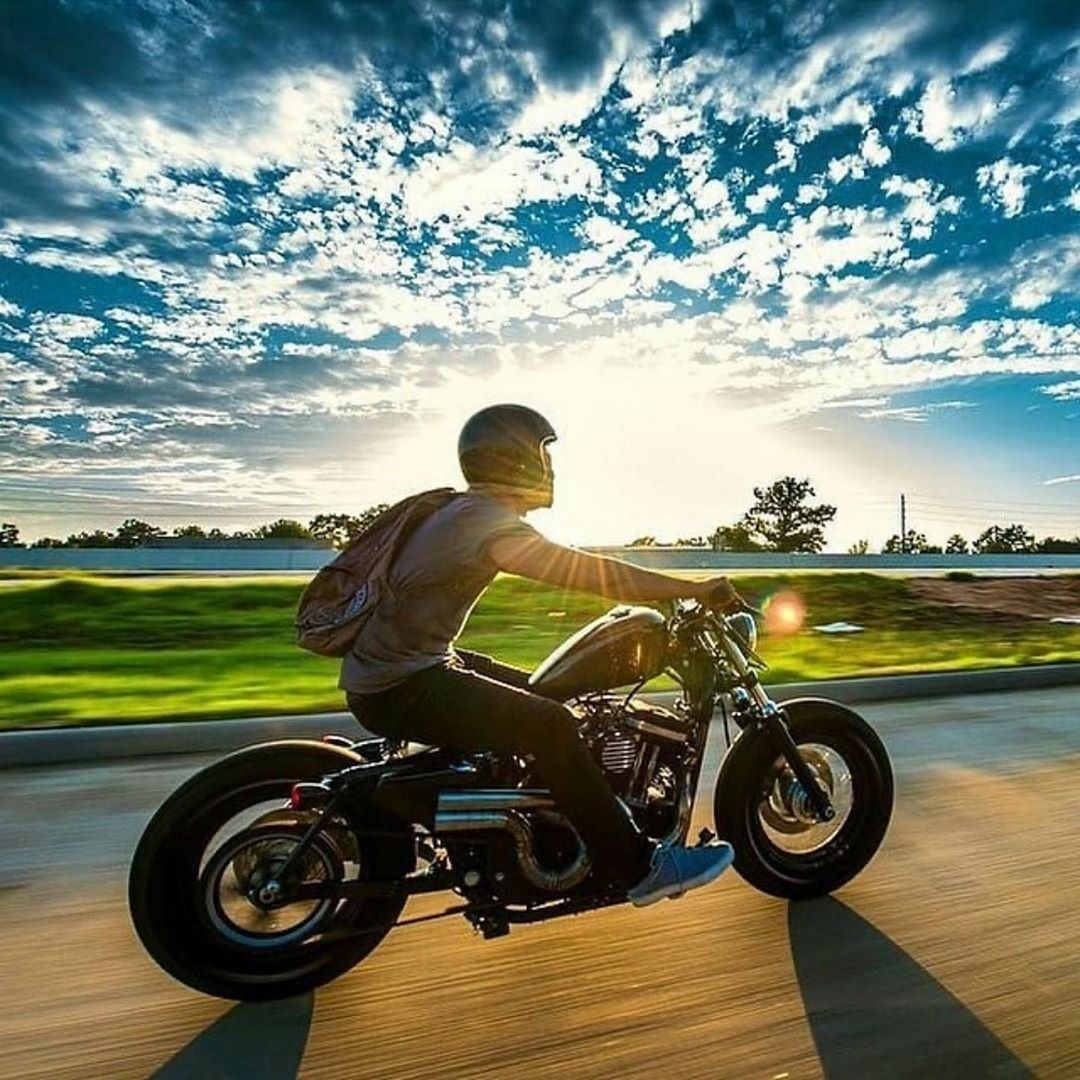 the manly life - man riding motorcycle sunset