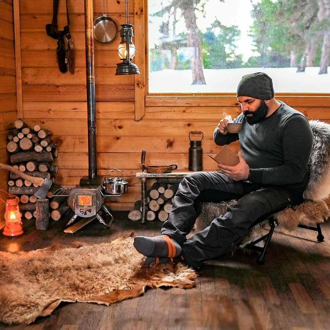 man reading and drinking coffee inside cabin