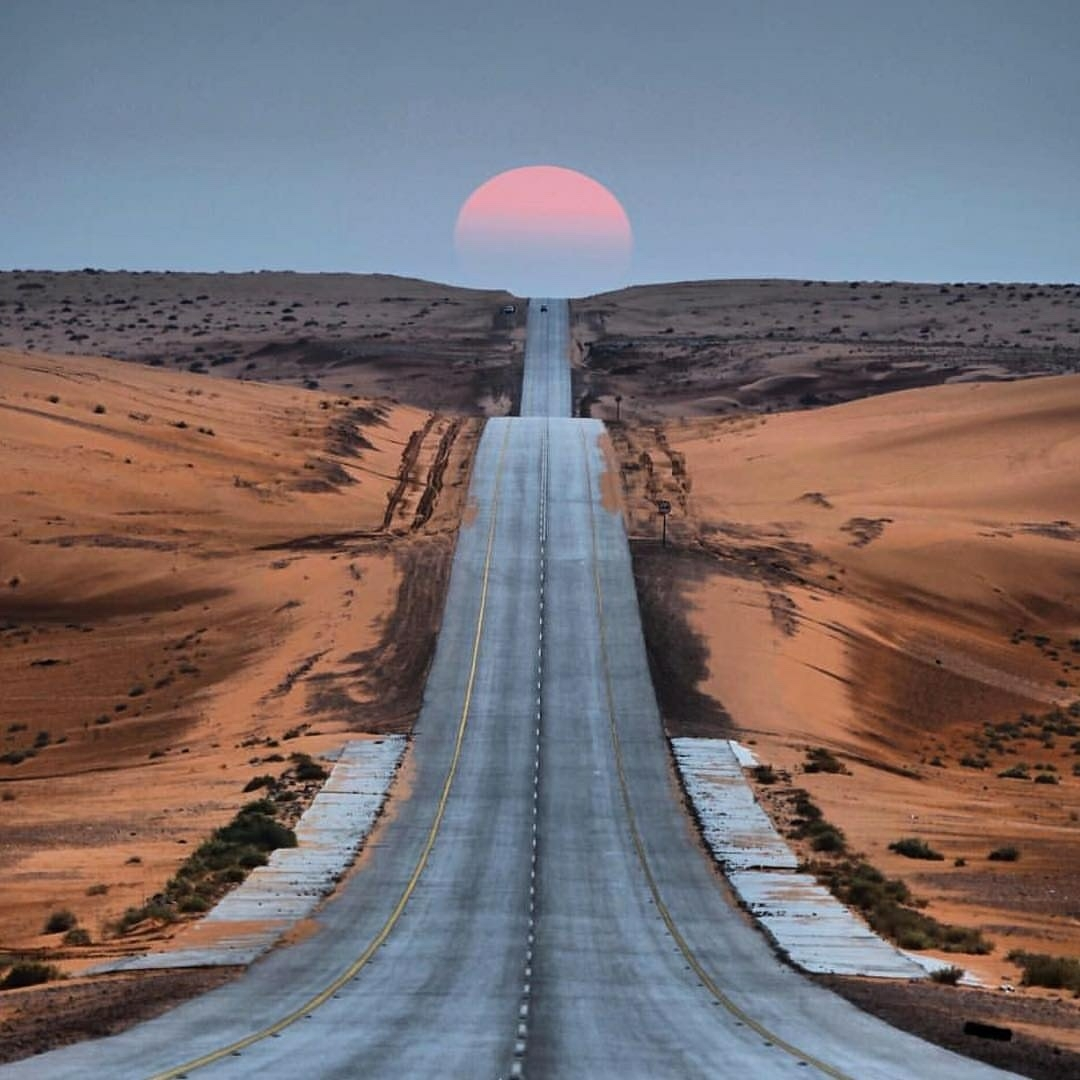long road with sun setting ahead