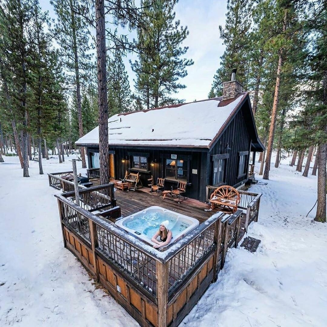 women in hot tub on cabin porch