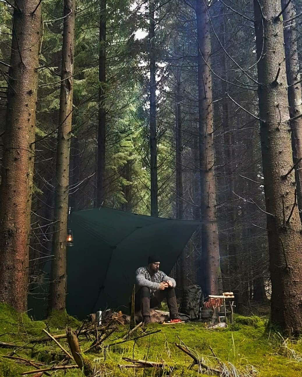 man sitting under shelter in woods