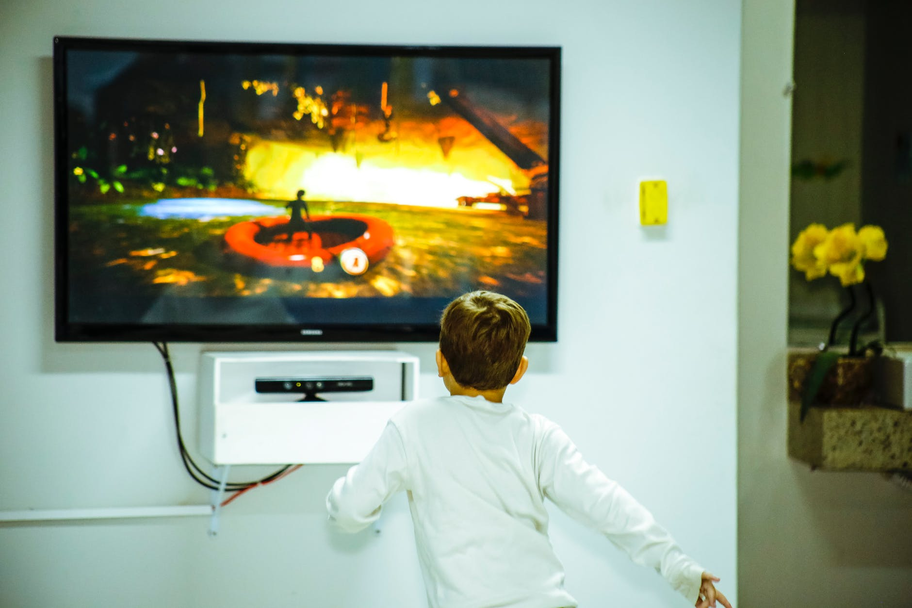boy standing in front of flat screen tv