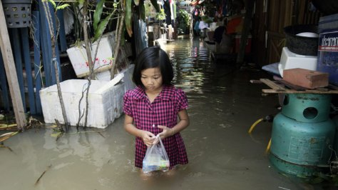 Thai girl walking through flood water