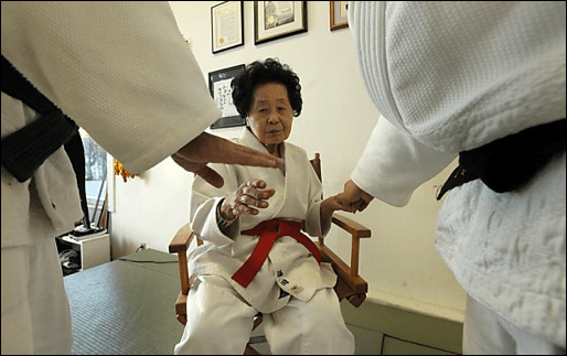 An elderly Japanese woman sits in a chair, holding out her hand. Other women's hands are held in front of her, copying her actions.