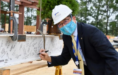 Beebe Healthcare CEO and President David Tam signs the beam before it's raised by a crane.