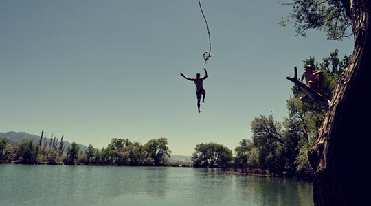 a person letting go of a rope swing over a lake