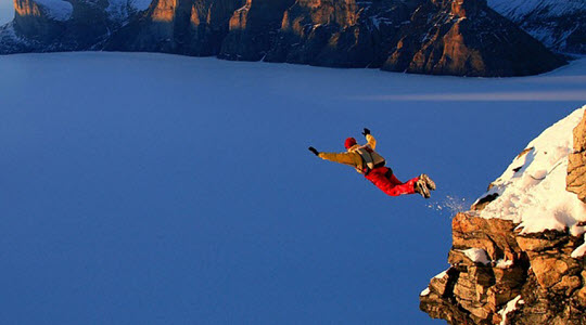 A base jumper leaping off a snowy ledge with the sea below