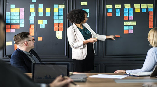 a woman pointing to post it notes in a business meeting
