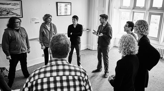 A group of people standing in a circle doing an improvisation exercise