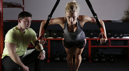woman balanced while hanging off rings while a trainer watches