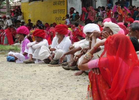 Men - most of them in brilliant turbans - sit and watch a performance in a village square near Ranakpur, Rajasthan.