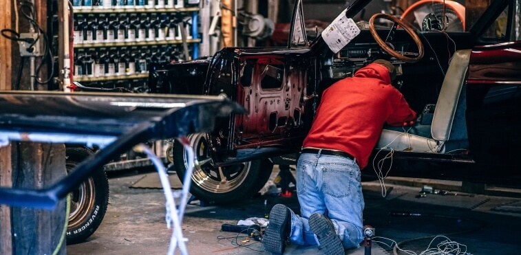 Auto mechanic troubleshooting an electrical problem