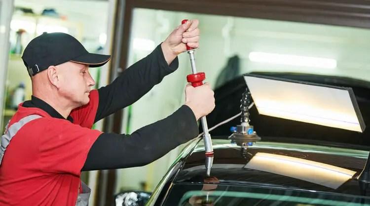 Paintless dent repair technician repairing a dent on a car