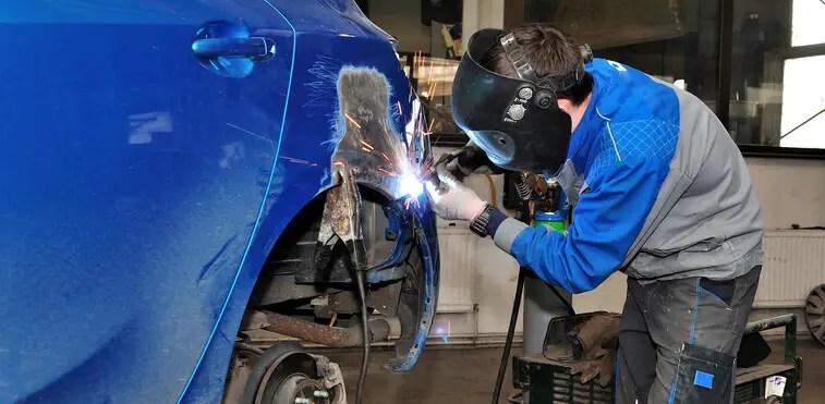 Auto body worker welding sheet metal