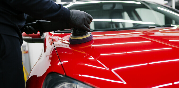 Car detailing specialist removing paint swirl using an orbital polisher