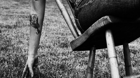 woman leaning back in a chair with her hand touching the grass