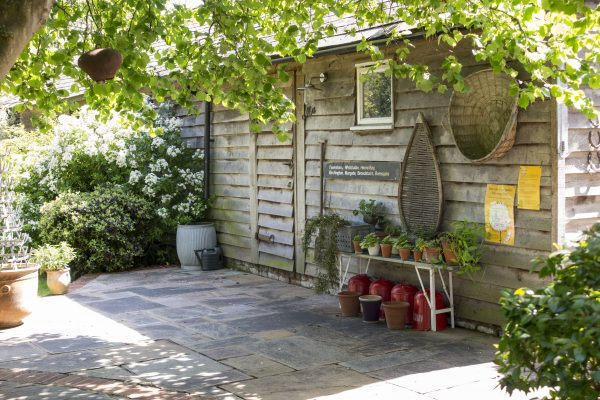 Add an old sign to your shed and display pots outside it