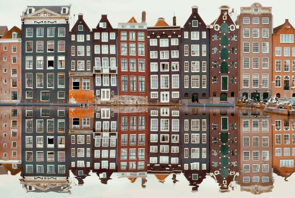 Amsterdam buildings reflected on a canal.