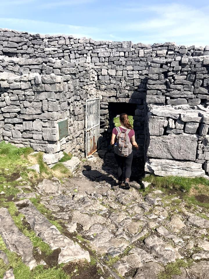 Woman in backpack walking through small stone door in Dun Aonghasa, Inis Mor, Ireland.