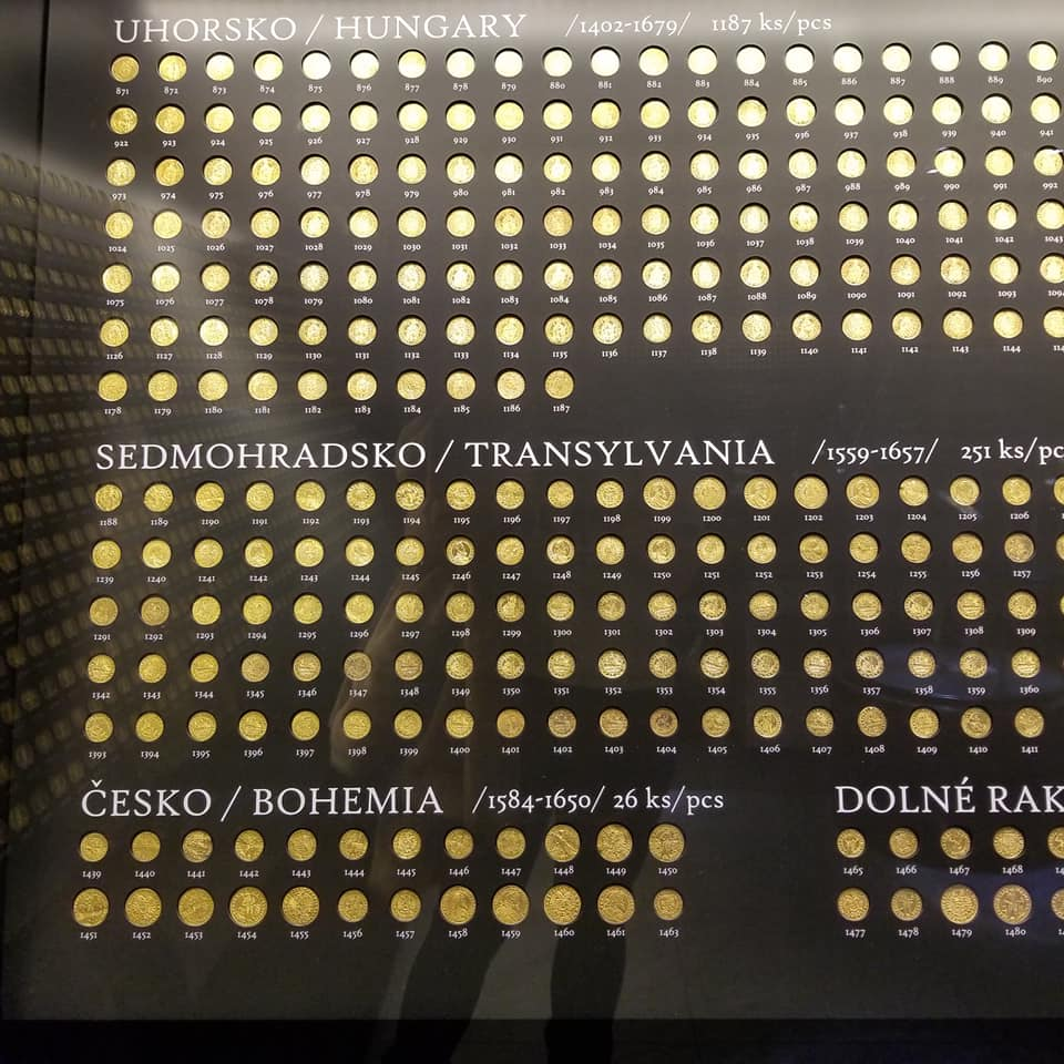 A display of the golden treasure of Kosice, Slovakia. There are between 2 and hundreds of golden coins displayed that were minted in different countries.