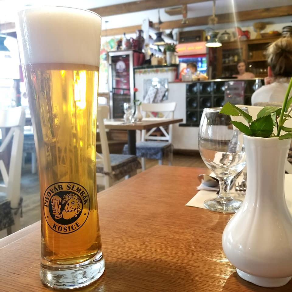 Close-up picture of a tall pale-colored beer with an inch and a half of head in a pilsner glass. Also on the table is an empty water glass and a small vase with a single red rose in it. Blurred in the background is the bar of the restaurant, empty.