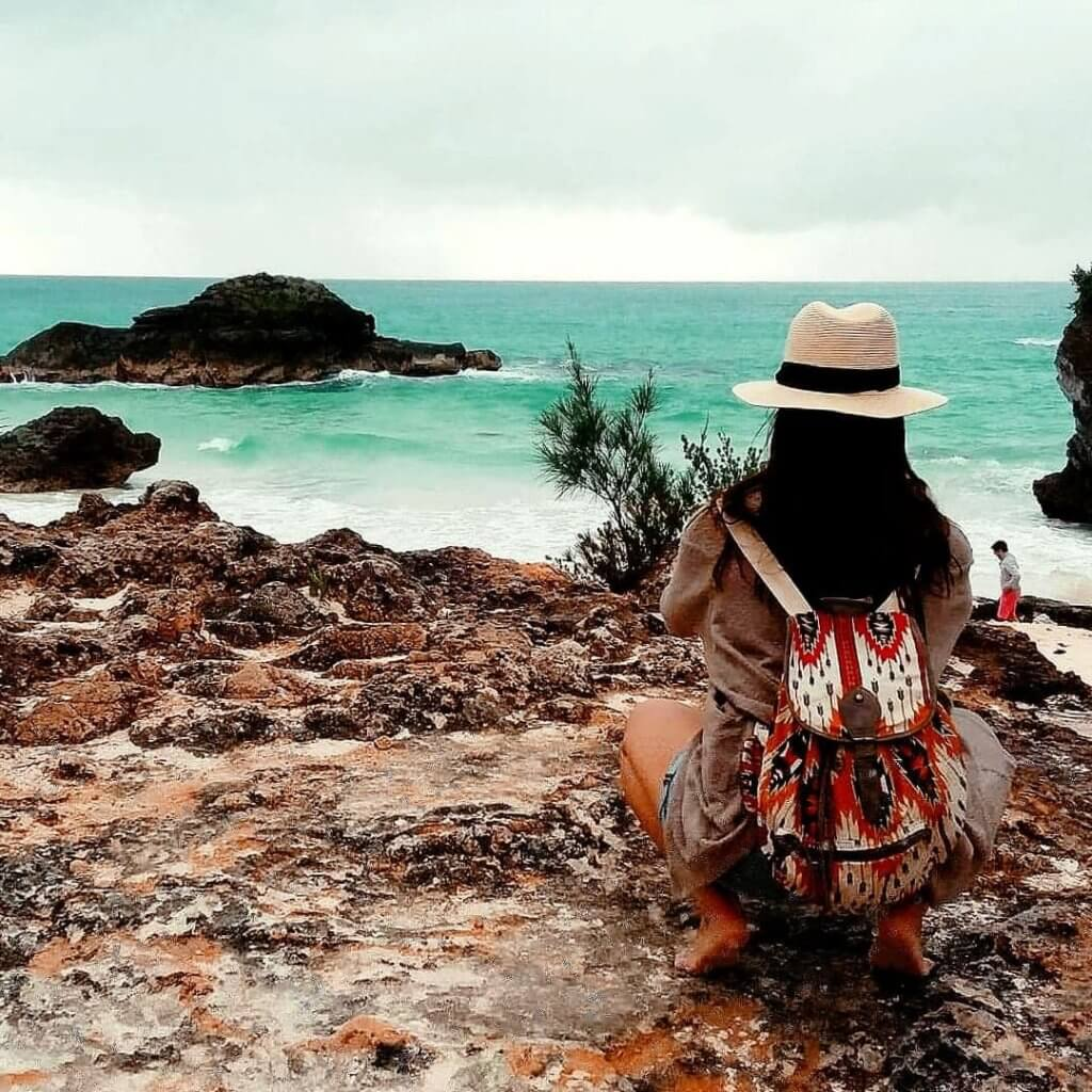 woman crouched down on rocks in bermuda taking a photo of horseshoe bay beach