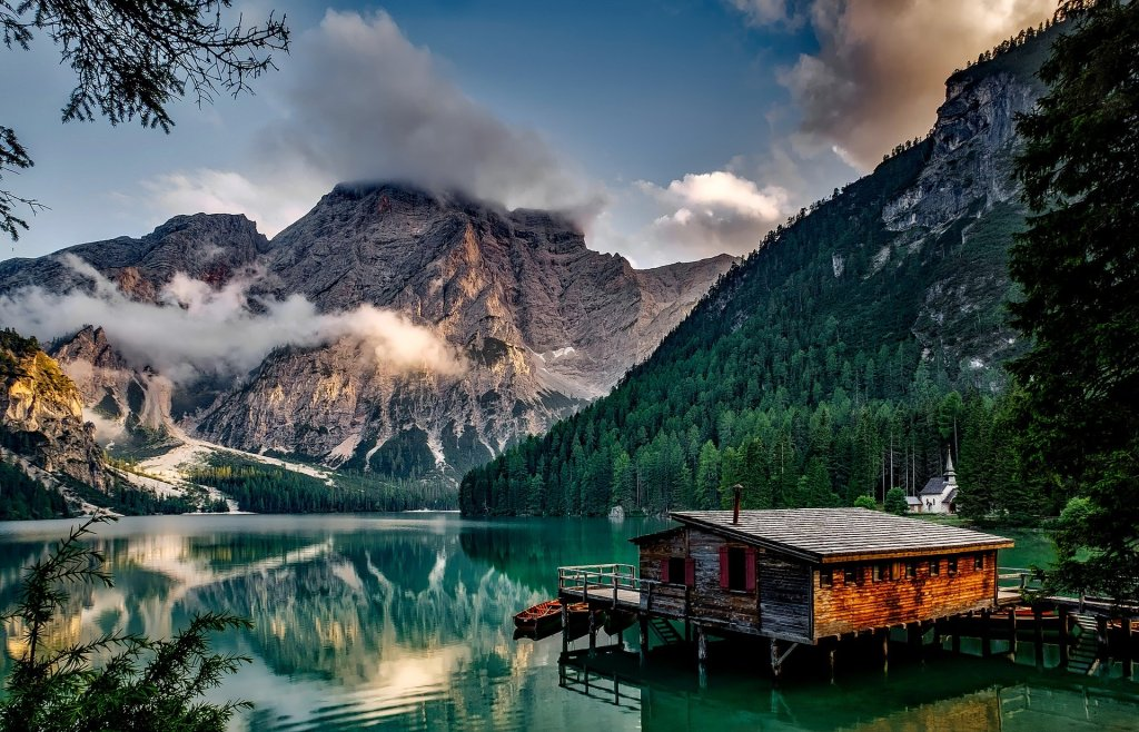 Small wooden hut in Lago di Braies, with turquoise waters and mountains in the background.